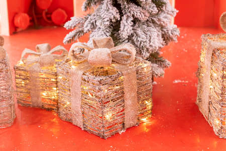 Christmas gifts made of metal and led light garland on red pedestal.Festive street decoration. Banque d'images