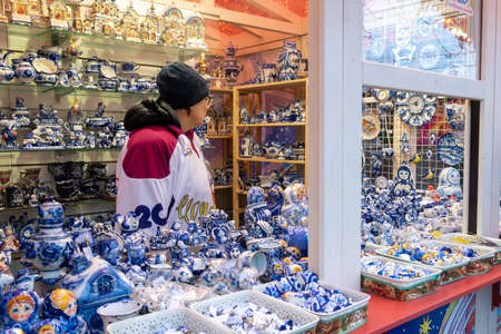 MOSCOW, RUSSIA - December 18, 2019: Colorful porcelain utensils and souvenirs in gzhel style at christmas fair. Traditional russian souvenir