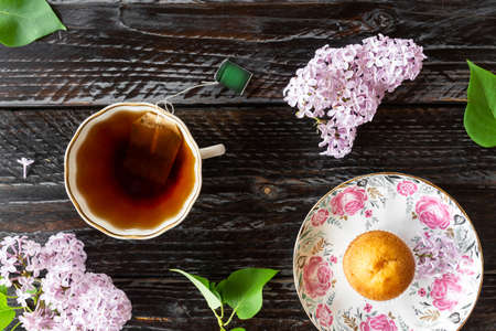 Top view of lilac flowers. cup of black tea and fresh homemade muffin on dark wooden background.