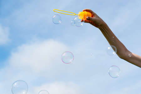 childs hand holding a wand for blowing soap bubbles against the blue sky on a sunny summer day