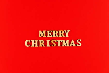 wooden letters on red background. Merry christmas lettering in red paper. Copy space.