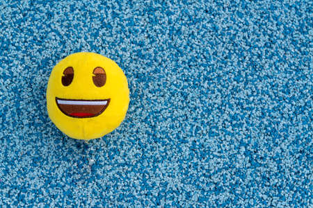 Toy textile yellow ball with smile on green background.
