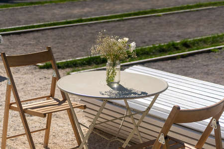 Street cafe. Wooden chairs and round metal table with bunch of flowers in a sunny day