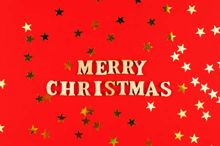 wooden letters on red background. Merry christmas lettering on red paper with scattered stars confetti. Festive greeting card