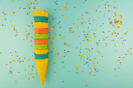 Set of various bright multicolored ice-cream waffle cones on blue background with scattered confetti sugar sprinkles