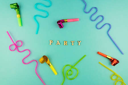 Bright festive party background - cocktail straws and party whistles on blue background