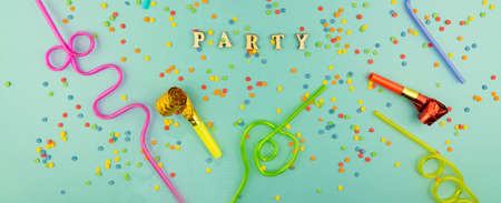 Bright festive party background - cocktail straws and party whistles on blue background with scattered sugar sprinkles