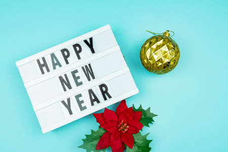 Happy new year light box with golden bauble and poinsettia on blue background Banco de Imagens