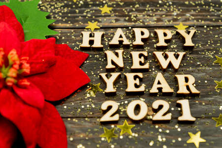 Happy New year 2021 celebration. Wooden text and poinsettia on wooden background. Flat lay Banco de Imagens