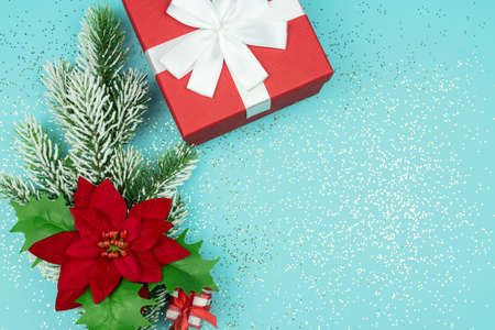 Top view of red gift box and fur tree branch with poinsettia on blue background with confetti. Festive Christmas greeting card Banco de Imagens