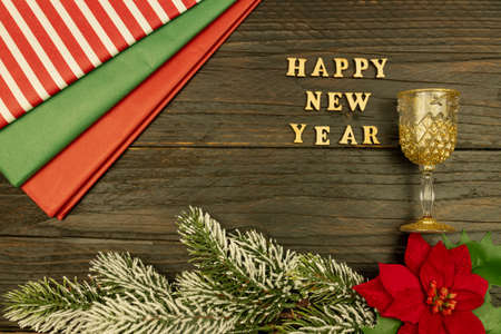 Happy New year 2021 celebration. Champagne glasses and poinsettia on wooden background. Flat lay