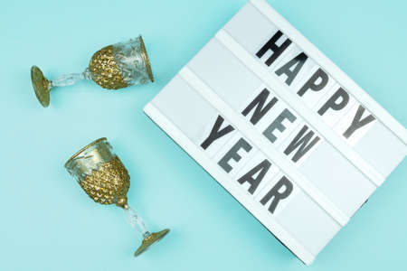 Happy new year light box with goldenchampagne glasses on blue background