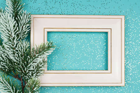 Festive greeting card for Christmas with photo frame, spruce tree branch on blue confetti background