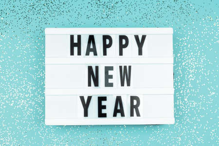 Happy new year light box with on blue background with scattered sparkling confetti Banco de Imagens