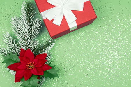 Top view of red gift box and fur tree branch with poinsettia on green background with confetti. Festive Christmas greeting card Banco de Imagens