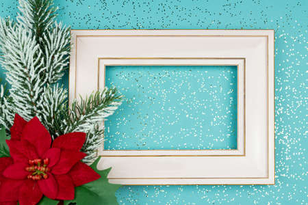 Festive greeting card for Christmas with photo frame, spruce tree branch and poinsettia on blue confetti background Banco de Imagens