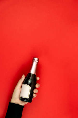 Female hand holding small champagne bottle on red, background. Mockup with copy space Stock fotó