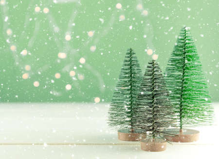 Miniature toy Christmas trees on a wooden table with snow. Imitation realistic scene. Banner.