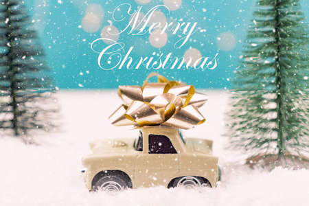 Christmas or New year card with toy car with golden bow and christmas tree miniatures and bokeh lights on background. Merry chritmas quote. Stock Photo