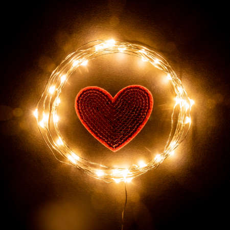 Red Heart in the circle of holiday celebration light garland on black background. Romantic Valentines day cards, invitations or posters. Dark mood