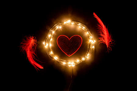 Red Heart in the circle of holiday celebration light garland with red feathers on black background. Romantic Valentines day cards, invitations or posters. Dark mood
