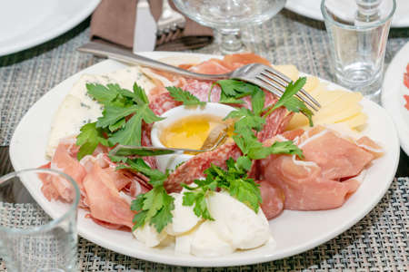 Close up of italian antipasto - assorted plate with cheese, ham, prosciutto and honey. Mediterranean appetizer.
