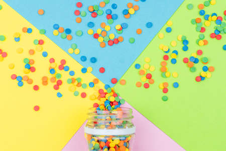 Pop colors. Festive multicolored background with bright sugar sprinkles scattered on paper