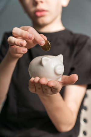 little kid investor putting a coin into piggy bank. saving money for future education concept.