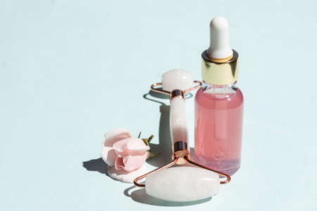 Cosmetic rose essential oil and rose quartz roller facial massager Gua-sha stone for facial beauty massage at home. Skin care and face treatment concept.