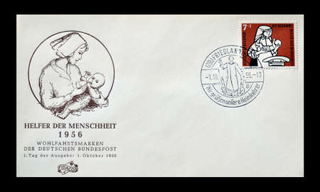 first day: Germany - First day cover letter with cancelled stamp that shows midwife weighing child, circa 1956.