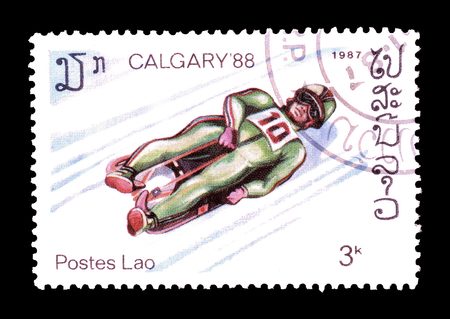 olympics: Cancelled postage stamp printed by Laos, that shows Toboggan in Winter Olympics, circa 1987.