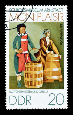 cooper: Cancelled postage stamp printed by German Democratic Republic, that shows Cooper and apprentice, circa 1974. Editorial