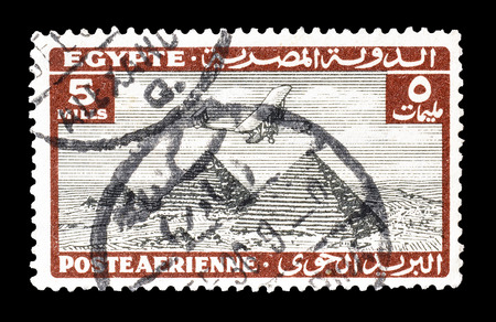 post stamp: Cancelled postage stamp printed by Egypt, that shows airplane over Giza pyramids, circa 1933.