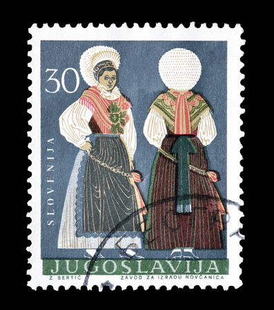 yugoslavia: Cancelled postage stamp printed by Yugoslavia, that shows traditional costume from Slovenia, circa 1964.