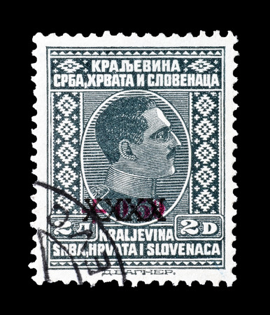 philately: Cancelled postage stamp printed by Yugoslavia, that shows overprinted portrait of king Alexander, circa 1928. Editorial