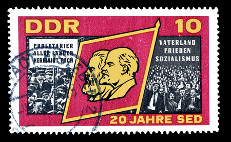 lenin: Cancelled postage stamp printed by German Democratic Republic, that shows  Marx, Lenin and crowd, circa 1966.