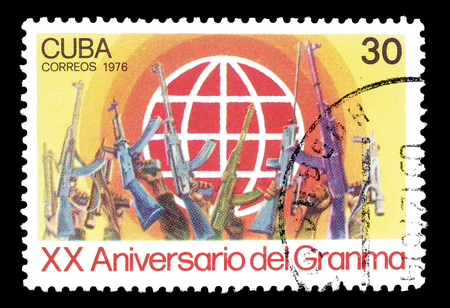 philately: Cancelled postage stamp printed by Cuba, that shows Globe and rifles, circa 1976. Editorial
