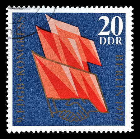 democratic: Cancelled postage stamp printed by German Democratic Republic, that shows flags and handshake, circa 1977. Editorial