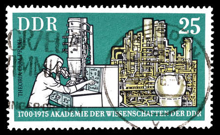 electrons: Cancelled postage stamp printed by German Democratic Republic, that shows Electron microscope and chemical plant, circa 1975.