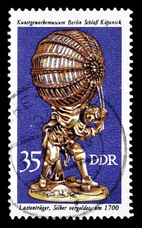 bearer: Cancelled postage stamp printed by German Democratic Republic, that shows Load bearer, circa 1976.