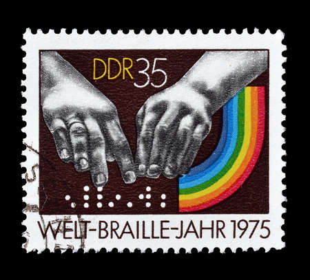 braille: Cancelled postage stamp printed by German Democratic Republic, that shows Braille dots and hands, circa 1975.