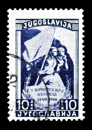 marchers: Cancelled postage stamp printed by Yugoslavia, that shows Marchers with party flag, circa 1948. Editorial