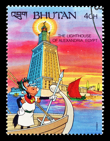 postage: Cancelled postage stamp printed by Bhutan, that shows Clarabelle cow visiting Lighthouse at Alexandria, circa 1991.