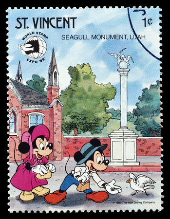 Cancelled postage stamp printed by Saint Vincent, that shows Mickey Mouse  and Minnie visiting Seagull monument, circa 1989. Editorial