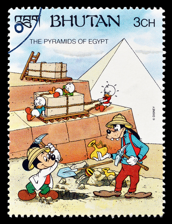 postage: Cancelled postage stamp printed by Bhutan, that shows Mickey Mouse and Goofy, visiting Pyramids, circa 1991.