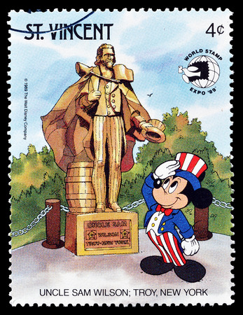 Cancelled postage stamp printed by Saint Vincent, that shows Mickey Mouse  visiting Uncle Sam Wilson monument, circa 1989. Editorial