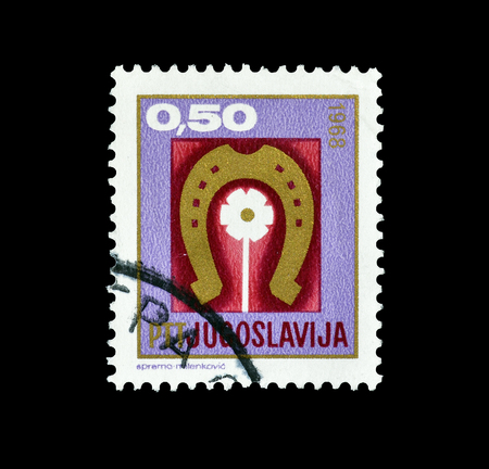 Cancelled postage stamp printed by Yugoslavia, that shows Horseshoe and flower, circa 1968.