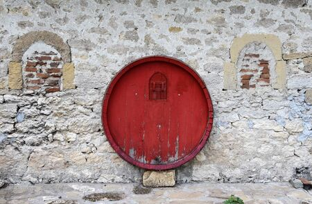 Red barrel on stone wall on wine house