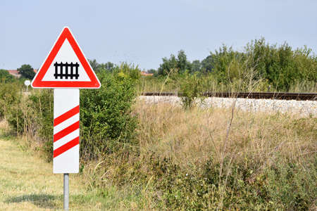 Warning road sign that informs driver of approaching railway crossing with ramp