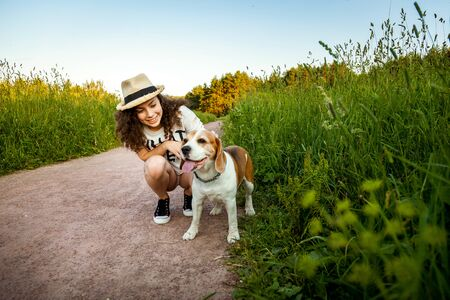 A girl with a dog on a forest path in the grass.